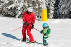 Ski class with ski instructor and little boy on mountain